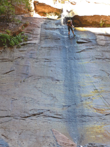 Hiker repelling down waterfall The Narrows Zion